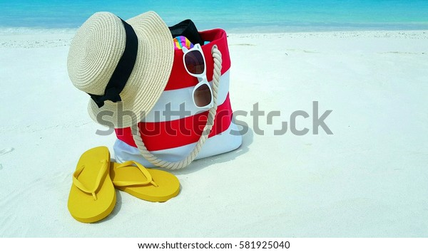 Bag on the white sandy beach with hat sunglasses and flip flop in summer holiday