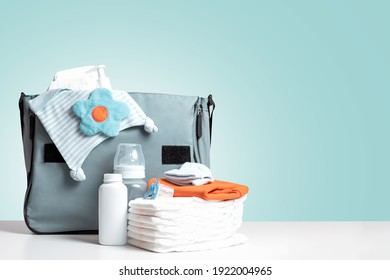 Bag packed for trip or journey or for walking with baby. Diapers, bottle and other necessary things for baby and mom. Diaper bag to maternity hospital. Copy space. Blue background.