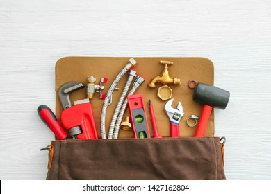 Bag with plumbing tools and items on white table