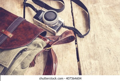 bag and retro camera on vintage wooden table background, traveling holiday photography concept