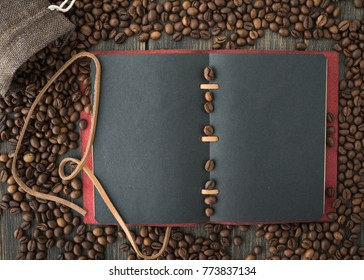 A bag of roasted arabica coffee beans and a dark paper note on a black wooden background top view