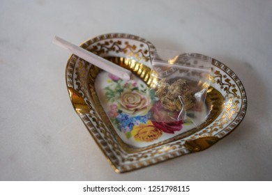 A bag of royal medical marijuana and a rolled joint in a heart shaped ashtray