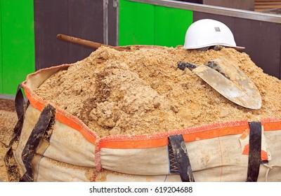 Bag of sand, shovel and helmet, break work on site construction