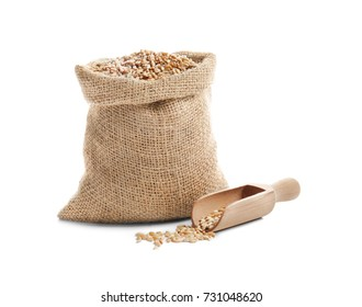 Bag and scoop with wheat grain on white background