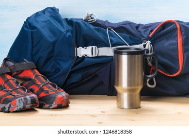 bag, shoes and a thermos for camping in the woods