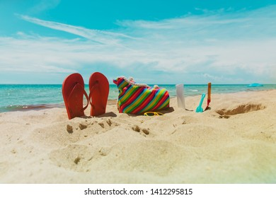bag, suncream, glasses and flip flops on beach