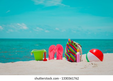 bag, suncream, toys and flip flops on beach