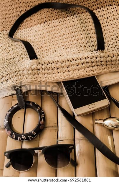 Bag wicker, glasses, bracelet, mobile phone, perfume on babmukovoy surface in natural tones