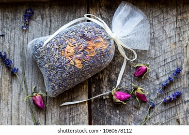 bag with wild roses petals and dried lavender flowers on wooden, vintage background - natural  fragrance to the wardrobe