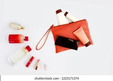 Bag with woman's cosmetics. Women's secrets. Deodorant, lipstick, eau de toilette, perfume, different care creams. Red bottles with cosmetics