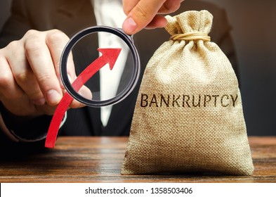 A bag with the word Bankruptcy and an up arrow in the hands of a businessman. The high level of bankruptcy in the country. The inability of the debtor to make payments on its debt obligations.