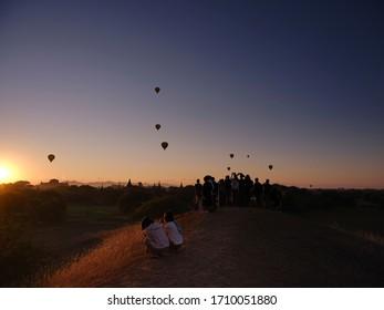 Bagan / Mandalay, Myanmar -  12 04 2019: Tourists watch air balloons in Bagan
