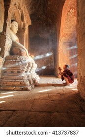 BAGAN, MYANMAR - April 2016: Monk burning candles in front of Buddha statue inside pagoda on April, 2016 in Bagan. Monks with light and Buddha are highlighted of Bagan.