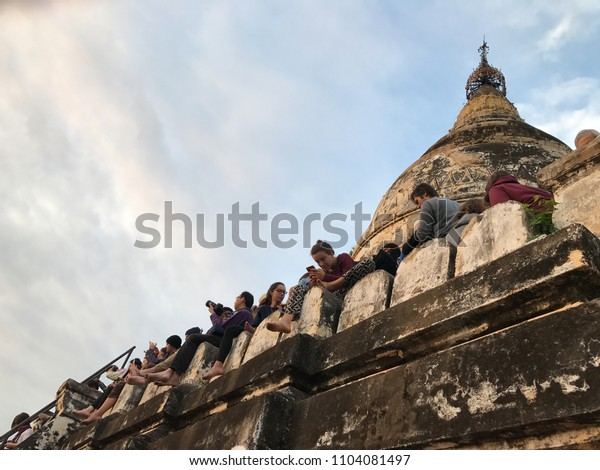Bagan, Myanmar - Dec 2016: Many tourists climbing up to top of Shwesandaw Pagoda to view and take photo of the scenic sunrise view of sea of pagoda