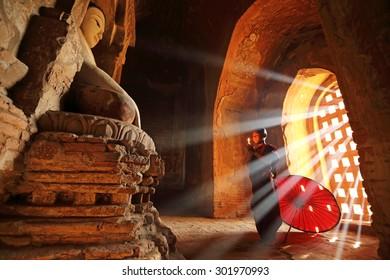 BAGAN, MYANMAR - DEC 6, 2014: Unidentified Buddhism neophyte prays in Buddihist temple on December 6, 2014 in Bagan, Myanmar. Southeast Asian neophyte praying in a Buddihist temple