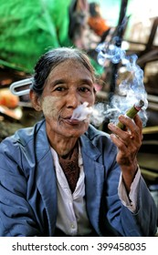 BAGAN, MYANMAR - DECEMBER 07, 2015: An old Myanmar woman smokes a handmade cigar. These cigars are a specialty of Yangon region.