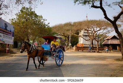 Bagan, Myanmar - Feb 17, 2016. A horse cart running on the rural road with many trees in Bagan, Myanmar. Bagan in central Burma is one of the worlds greatest archeological sites.