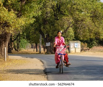 Bagan, Myanmar - Feb 19, 2016. A Burmese girl biking on rural road in Bagan, Myanmar. Bagan is home to the largest and densest concentration of Buddhist temples, pagodas and stupas.