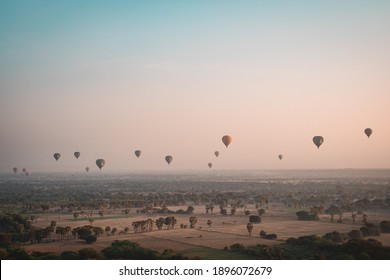 BAGAN, MYANMAR - JANUARY 22, 2020: A group of hot air balloons flying above the fields of Bagan, Myanmar at sunrise.