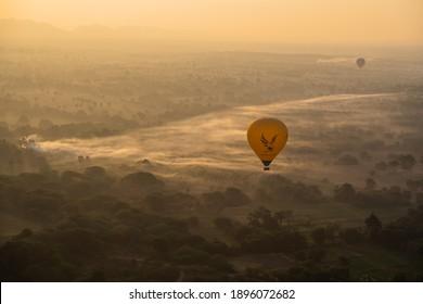 BAGAN, MYANMAR - JANUARY 22, 2020: Yellow hot air balloon flys low above misty fields during sunrise over Bagan, Myanmar.