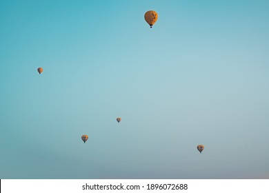 BAGAN, MYANMAR - JANUARY 22, 2020: Five multi-colored hot air balloons in flight above Bagan, Myanmar with a clear blue sky.