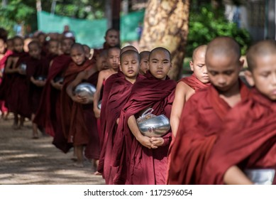 BAGAN, MYANMAR - JUL 18, 2018: Buddhist novices walk to collect alms and offerings along the road at Bagan, Myanmar.