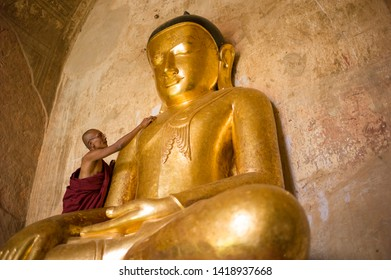 Bagan, Myanmar - March 2 2015: The  monk is worshiping and stick gold leaf on the Buddha statue in Sulamani Temple.