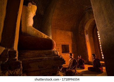 BAGAN, MYANMAR - May 5, 2019:A Monks respect Ancient buddha statue at Dhammayangyi Temple a Buddhist temple located in Bagan, Myanmar