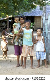 BAGAN, MYANMAR - OCT 16: Children stand barefoot outside their family hut in Bagan, Myanmar on October 16, 2011. Currently 26% of the Myanmar population is living below the poverty line.