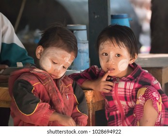 BAGAN, MYANMAR-DECEMBER 04,2017: A girl with tanaka on her face sit on wood chair and a boy in local coffee shop in the morning.