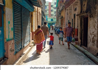 Bagbazar, Kolkata, India, 15.10.2018. A street scene of the early morning of north Kolkata. A boy with his dad and a girl with her mom is walking in a narrow lane. Indian street and lifestyle
