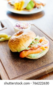 Bagel bread with smoked salmon meat and vegetable on wooden cutting board