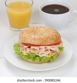 Bagel for breakfast with ham, cream cheese, tomatoes, lettuce, orange juice and coffee