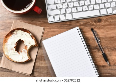 A bagel with cream cheese and a bite taken out next to a computer keyboard and a pad and pen. A cup of coffee in the upper corner, Horizontal for a high angle.