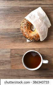 A bagel and a cup of coffee viewed from a high angle. Vertical format with copy space.