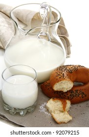 Bagel with poppy seeds a pitcher of milk on a white background.