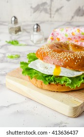 Bagel sandwich with salad and eggs on marble background. Selective focus