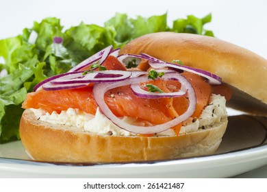 Bagel with Smoked Salmon Lox, cream cheese and red onion accompanied by lettuce salad.
