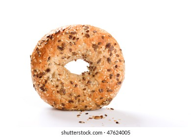 Bagel stood on edge with seeds in foreground