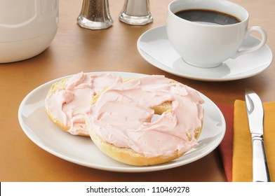 A bagel with strawberry cream cheese and coffee