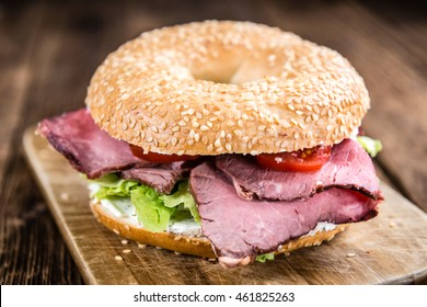 Bagel (with Roast Beef) on vintage background (selective focus; close-up shot)
