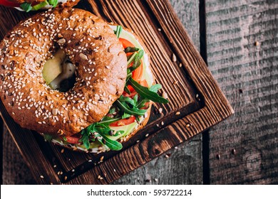 Bagels with cream, avocado, tomatos and arugula on wooden board and table background. Healthy breakfast food. Top view and Copy space