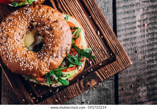 木のボードとテーブルの背景にベーグルとクリーム、アボカド、トマト、アルゴラ。健康的な朝食。上面図とコピースペース