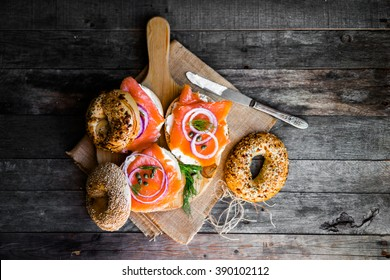 Bagels with cream cheese and smoked salmon on rustic wooden background