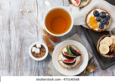 Bagels with different toppings - with cream cheese, figs, bananas, chocolate, blueberries for breakfast and a cup of tea on a rustic wooden table, top view