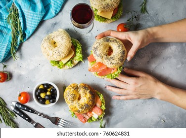 Bagels with salmon, vegetables, cream-cheese and glass of red wine on grey concrete background. Woman hands hold bagel.