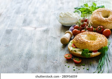 Bagels sandwiches with cream cheese, tomatoes and chives copy space
