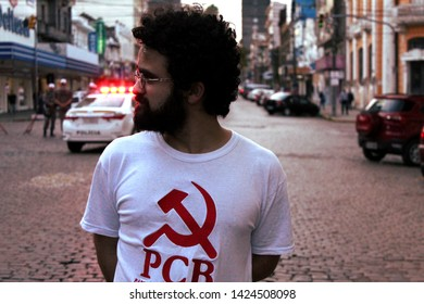 Bage/Rio Grande do Sul/Brazil - 06/14/2019: Political activist of the Brazilian Communist Party on the street against the pension reform in Brazil with the police reprimanding force behind.