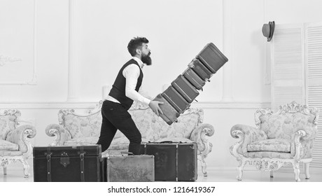 Baggage insurance concept. Man with beard and mustache in classic suit delivers luggage, luxury white interior background. Porter, butler accidentally stumbled, dropping pile of vintage suitcases.