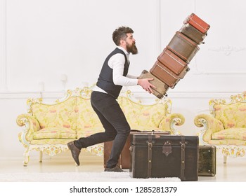 Baggage insurance concept. Porter, butler accidentally stumbled, dropping pile of vintage suitcases. Man with beard and mustache in classic suit delivers luggage, luxury white interior background.